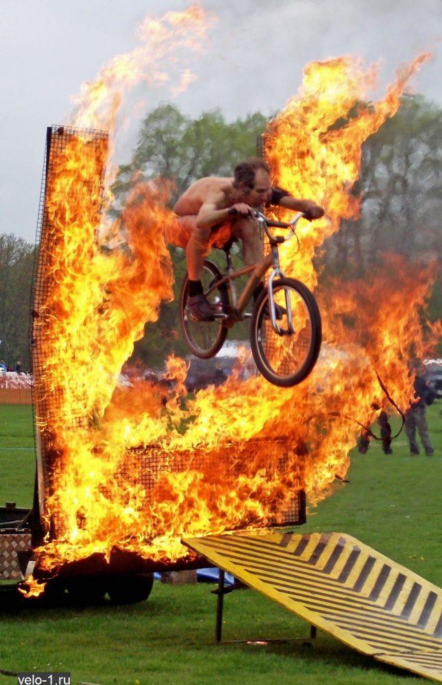 Мужик на велосипеде прыгает через огонь