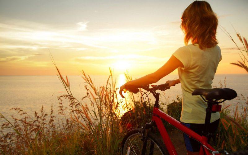 Девушка с велосипедом у моря смотрит на восход, обои на рабочий стол